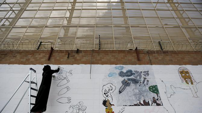 Pro-Houthi activist paints graffiti depicting Saudi-led air strikes on the wall of the Saudi embassy in Sanaa