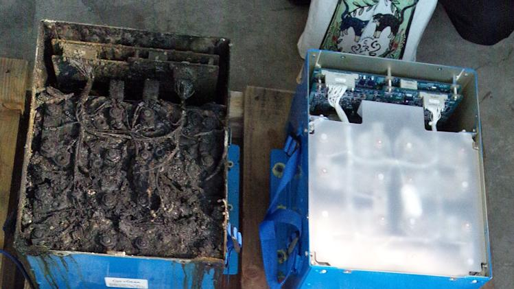 This Jan. 17, 2013 photo provided by the Japan Transport Safety Board shows the distorted main lithium-ion battery and its lid, left, of the All Nippon Airways' Boeing 787 which made an emergency landing on Wednesday, Jan. 16, 2013 at Takamatsu airport in Takamatsu, western Japan. At right are the model in normal condition. U.S. safety officials and Boeing inspectors joined a Japanese investigation Friday into the 787 jet at the center of a worldwide grounding of the technologically advanced aircraft. The pilot of the ANA plane made an emergency landing Wednesday morning after he smelled something burning and received a cockpit warning of battery problems. All passengers evacuated the plane on emergency slides. (AP Photo/Japan Transport Safety Board) EDITORIAL USE ONLY, NO SALES