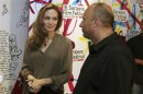 U.S. actress Angelina Jolie stands next to Mirsad Purivatra, director of the 18th Sarajevo Film Festival, before the festival