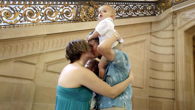 Kim, at right, and Rachel Hadley kiss as they hold their one-year old twins Sidney, center, and Phin, top right, after they were married at City Hall in San Francisco, Saturday, June 29, 2013. Less than 24 hours after California started issuing marriage licenses to same-sex couples, lawyers for the sponsors of the state's gay marriage ban filed an emergency motion Saturday asking the U.S. Supreme Court to step in and stop the weddings. (AP Photo/Marcio Jose Sanchez)