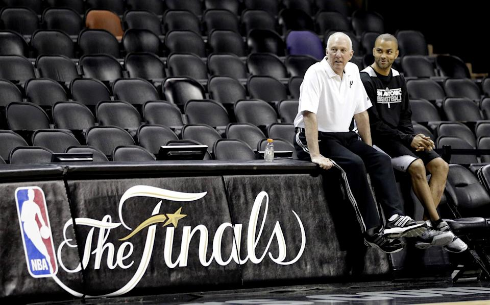 San Antonio Spurs' Tony Parker, right, sits with coach Gregg Popovich during NBA basketball practice Wednesday, June 12, 2013, in San Antonio. The Spurs lead the Miami Heat 2-1 in the best-of-seven games series. Game 4 of the NBA finals series is scheduled for Thursday. (AP Photo/David J. Phillip)