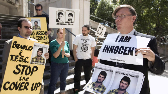 FILE - In this Oct. 6, 2010, file photo, Scott Cobb, right, joins about 15 members of The Campaign to End the Death Penalty at a protest before a hearing about the Cameron Todd Willingham case outside the Blackwell-Thurman Criminal Justice Center in Austin, Texas. The Innocence Project said Friday, Feb. 28, 2014, that newly discovered documents undermine the credibility of a key witness against Willingham who was controversially executed on Feb. 17, 2004. (AP Photo/Statesman.com, Jay Janner, File) MAGS OUT; INTERNET AND TV MUST CREDIT PHOTOGRAPHER AND STATESMAN.COM