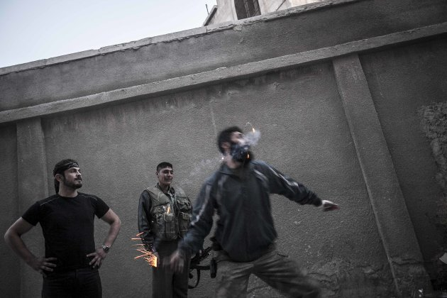 In this Sunday, Oct. 28, 2012 photo. A rebel fighter throws a homemade grenade towards Syrian army troops on the frontline in the Bustan Al-Pasha neighborhood of Aleppo, Syria. Syria's air force fired missiles and dropped barrel bombs on rebel strongholds while opposition fighters attacked regime positions, flouting a U.N.-backed cease-fire that was supposed to quiet fighting over a long holiday weekend but never took hold. (AP Photo/Narciso Contreras).