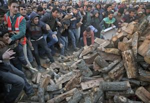 Migrants mob a truck bringing donated firewood at the …
