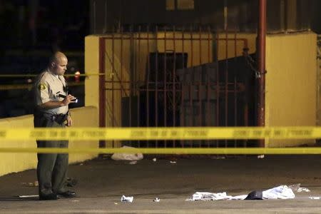 """Los Angeles County Sheriff's deputy inspects the scene where a pedestrian was killed in a hit-and-run crash reportedly involving rap mogul Marion """"Suge"""" Knight, in Compton, California"""