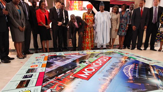 Babatunde Raji Fashola, Lagos state governor, center, rolls a dice during the presentation of a Lagos-themed Monopoly board game in Lagos, Nigeria, Tuesday, Dec. 11, 2012. Nigeria's largest city of Lagos is no boardwalk, but now Monopoly is taking an inspiration from the sprawling chaos.  (AP Photo / Sunday Alamba )