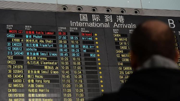 People stand beside the arrival board showing the missing Malaysia Airlines Boeing 777-200 plane at Beijing Airport on March 8, 2014