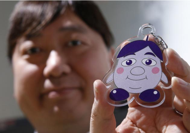 "President of the professional soccer club Sanfrecce Hiroshima, Kaoru Koyano, poses with the team's mascot key ring called ""Koyanon"" which features himself as a mascot at the Japan Footba"