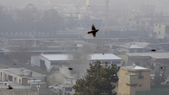 Dust rises from the site where a rocket fired by militants landed, as birds fly near the Kabul traffic police headquarters as it is attacked in Kabul, Afghanistan, Monday, Jan. 21, 2013. Taliban insurgents wearing suicide vests attacked the Kabul traffic police headquarters before dawn Monday, police said, and eyewitnesses heard numerous explosions while a gun battle was still raging nearly four hours later. (AP Photo/Musadeq Sadeq)