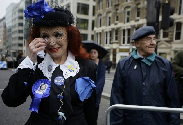 Supporter of former British prime minister Thatcher wipes her tears as she joins others by the route of the funeral procession at St Paul's Cathedral in London