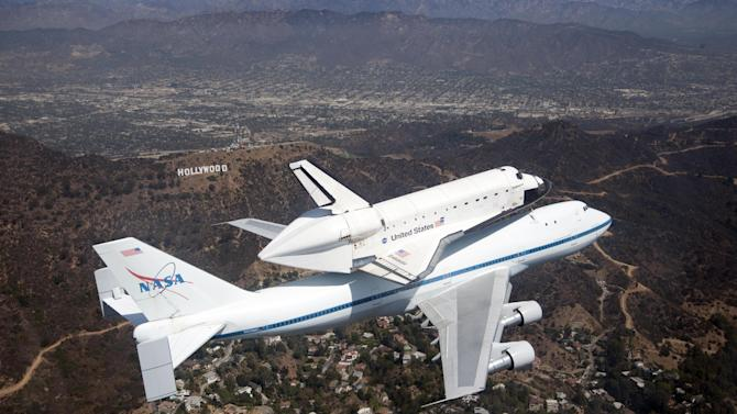 In this photo provided by NASA, space shuttle Endeavour and its modified 747 carrier aircraft soar over the Hollywood sign in Los Angeles during its tour of California, Friday, Sept. 21, 2012. (AP Photo/NASA, Jim Ross)