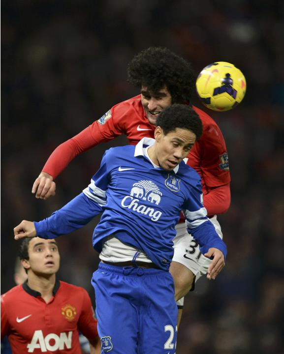 Manchester United's Marouane Fellaini challenges Everton's Steven Pienaar during their English Premier League soccer match in Manchester, northern England