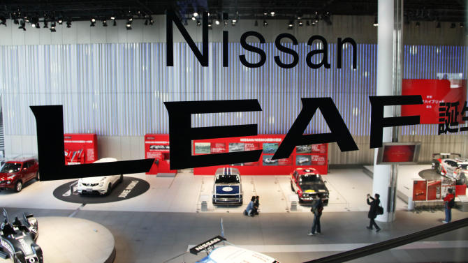 Visitors tour a gallery displaying old Nissan rally cars behind a transparent sign promoting its latest electric car at the headquarters of Nissan Motor Co. in Yokohama, Japan, Friday, Feb. 8, 2013. The Japanese auto maker suffered a 34.6 percent plunge in October-December profit to 54.1 billion yen (US$579 million) as global sales languished, especially in China, where anti-Japanese sentiment flared over a territorial dispute. (AP Photo/Koji Sasahara)