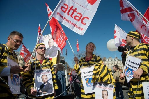 <p>People dressed in prisoner costumes and holding placards with a picture of France's President Francois Hollande take part in a demonstration called by leftist parties against austerity measures on September 30 in Paris.</p>