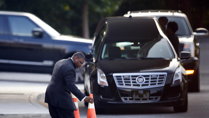 A man places cones in front of a hearse before a memorial service for Bobbi Kristina Brown Saturday, Aug. 1, 2015, in Alpharetta, Ga.  Brown, the only child of Whitney Houston and R&B singer Bobby Brown, died in hospice care July 26, about six months after she was found face-down and unresponsive in a bathtub in her suburban Atlanta townhome.  (AP Photo/John Bazemore)