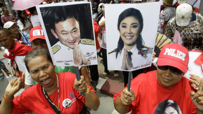 FILE - In this Aug. 5, 2011 file photo, supporters of Pheu Thai Party, holding portraits of former Thai Prime Minister Thaksin Shinawatra, left, and his sister Yingluck Shinawatra, cheer outside Parliament in Bangkok, Thailand.  Yingluck marks a year in office this weekend as Thailand's first female prime minister. Her achievement is all the more remarkable because she is the sister of the man at the center of Thailand's long-running political maelstrom, who was deposed by a military coup in 2006 after being accused of corruption and disrespect for King Bhumibol Adulyadej. (AP Photo/Sakchai Lalit, File)