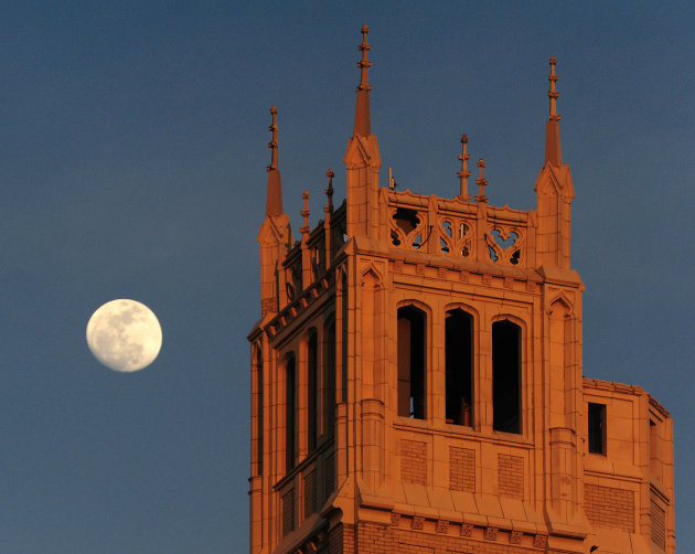In this Thursday, March 17, 2011 picture, the moon rises above the Jackson Building tower in downtown Asheville, N.C. as the building is bathed in orange light from the setting sun. There's a full moo