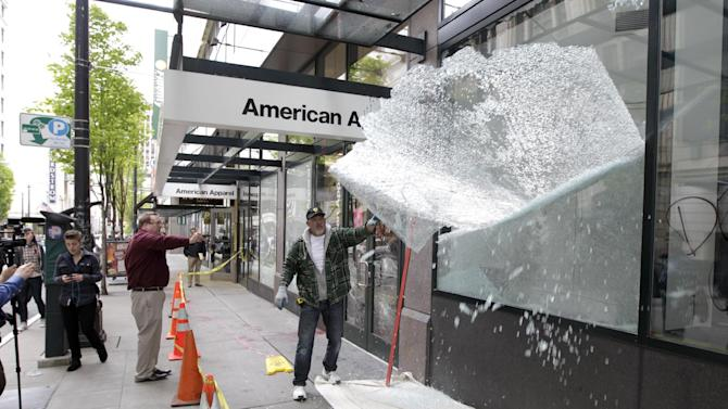 A worker removes a shattered window from a Niketown store, Tuesday, May 1, 2012, after after it was damaged during May Day protests in downtown Seattle. Activists staged May Day demonstrations around the world on Tuesday to recognize a day traditionally associated with labor and workers' rights. (AP Photo/Ted S. Warren)