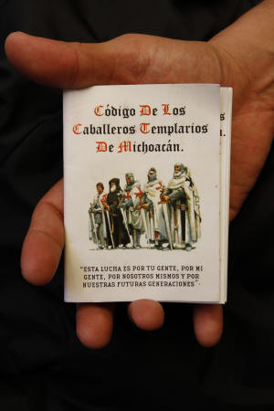 A man holds up a copy of the 'The Code of the Knights Templar of Michoacan',  in Morelia, Mexico, Tuesday, July 19, 2011. The professionally printed, pocket-size booklet was obtained by the Associated Press by a person who did not want to be identified and who said it was distributed earlier this month by two men in regular clothing aboard a bus traveling in rural Michoacan. (AP Photo/Marco Ugarte)