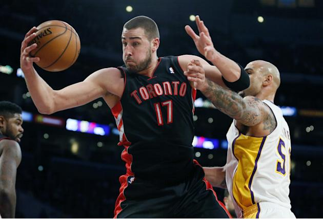 Toronto Raptors' Jonas Valanciunas, left, of Lithuania, brings in a defensive rebound in front of Los Angeles Lakers' Robert Sacre, right, during the first half of an NBA basketball game in Lo