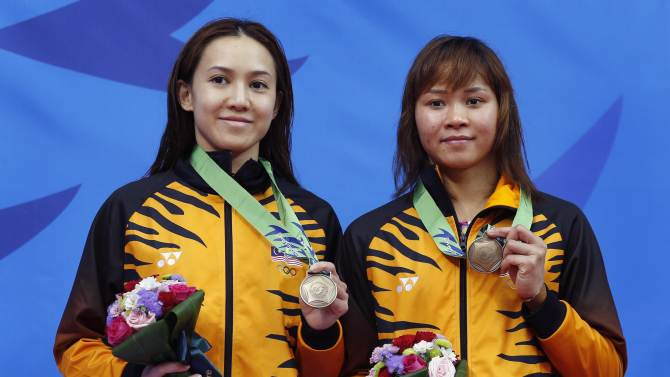 Malaysia's bronze medalists Leong and Pamg pose during the victory ceremony for the Women's 10m Synchronised Platform diving final during the 17th Asian Games in Incheon