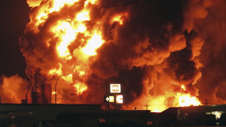 A fire burns in an industrial part of Williston, N.D. in the early hours of Tuesday, July 22, 2014. The site is near three oil companies and a rail line, just east of Williston's downtown. Explosions could be seen and heard at the scene. Police attributed them to barrels but didn't immediately say what was in them. No injuries were immediately reported. (AP Photo/Josh Wood)