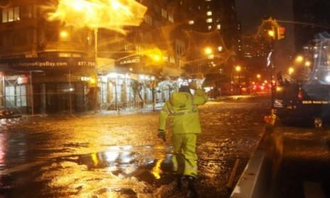 A Con Edison worker walks through the flood waters in front of NYU Langone Medical Center during Hurricane Sandy on Oct. 29.
