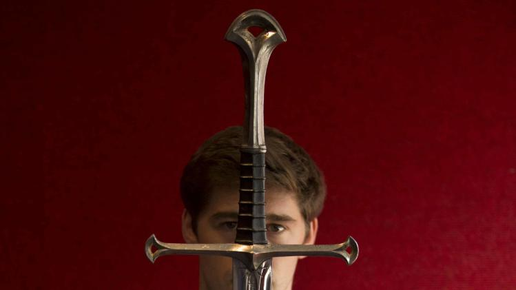 A gallery assistant poses for a photograph with the sword 'Anduril' which was used in the Lord of the Rings film 'Return of the King' in Bonhams Auction house in London