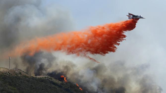 A water bomber makes a drop on flames burning on a hillside as the Cocos Fire continues in San Marcos