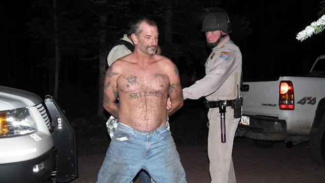 In this Aug. 19, 2010 file photo provided by the U.S. Marshals Service, fugitive John McCluskey is taken into custody by U.S. Marshals in eastern Arizona. A jury on Monday, Oct. 7, 2013 convicted McCluskey of capital murder, carjacking, and other charges in the killings of Gary and Linda Haas of Tecumseh, Okla., who crossed paths with him and two other fugitives on a New Mexico highway. He faces life in prison or the death penalty. (AP Photo/U.S. Marshals Office, File)