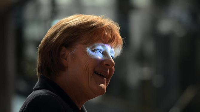 German chancellor Angela Merkel smiles as she is illuminated by a beamer as she arrives for a ceremony of the association of welfare organizations BAGFW in Berlin, Tuesday, Nov. 27, 2012. (AP Photo/Johannes Eisele, pool)