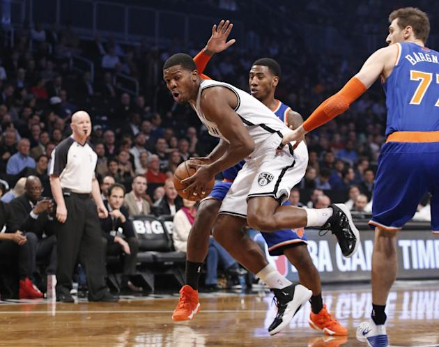 New York Knicks guard Iman Shumpert  defends Brooklyn Nets shooting guard Joe Johnson (7) as New York Knicks forward Andrea Bargnani , right, looks on from the floor in the first half of their NBA bas