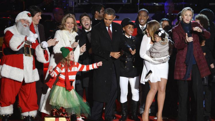 U.S. President Obama dances with entertainers on stage at the end of the National Christmas Tree Lighting ceremony in Washington