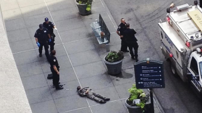 New York City police approach the lifeless body of Jeffrey Johnson lying on a sidewalk near the Empire State Building in New York following a shooting Friday, Aug. 24, 2012. Police say 58-year-old Johnson, who was laid off from a nearby shop in 2011, shot a former colleague to death near the iconic skyscraper, then randomly opened fire on people nearby before firing on police. New York City Mayor Michael Bloomberg said some of the victims may have been hit by police bullets as police and the gunman exchanged fire. (AP Photo/Guillermo Ratzlaff)