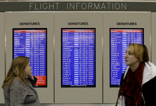 A flight information screen displays canceled flights as passenger walk at Midway airport in Chicago, Thursday, Dec. 20, 2012. The first widespread snowstorm of the season crawled across the Midwest on Thursday, with whiteout conditions stranding holiday travelers. The storm led airlines to cancel about 1,000 flights ahead of the Christmas holiday — relatively few compared to past big storms, though the number was climbing. Southwest Airlines scratched all of its flights scheduled after 4:30 p.m. today at Midway. (AP Photo/Nam Y. Huh)