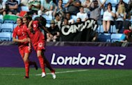 Canada's forward Christine Sinclair (R) celebrates with a teammate after scoring during the London 2012 Olympic women's football match at The City of Coventry Stadium in Coventry, central England. Canada won 3-0