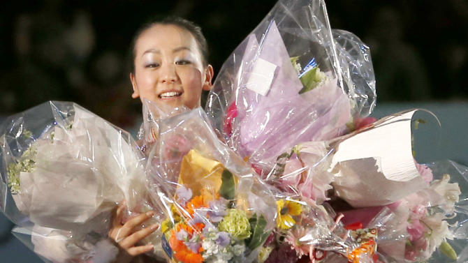 Winner Mao Asada holds bouquets of flowers she was presented from fans after the awarding ceremony of women's events of the ISU Four Continents Figure Skating Championships in Osaka, Japan, Sunday, Feb. 10, 2013. (AP Photo/Shizuo Kambayashi)