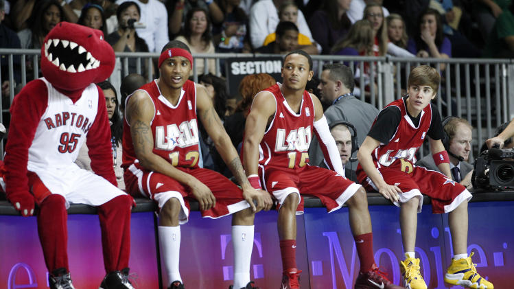 From right to left, singers Justin Bieber, Romeo Miller, Trey Songz watch during a BBVA All-Star celebrity basketball game with the Toronto Raptors mascot at the NBA All Star Weekend in Los Angeles, Friday, Feb. 18, 2011. (AP Photo/Jae C. Hong)