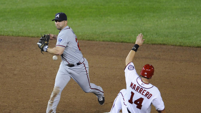 Washington Nationals' Chris Marrero (14) is called out at second as Atlanta Braves second baseman Dan Uggla, left, loses control of the ball after he touched the bag and was unable to get Ian Desmond out at first during the ninth inning of a baseball game on Friday, Sept. 23, 2011, in Washington. The Braves won 7-4. (AP Photo/Nick Wass)