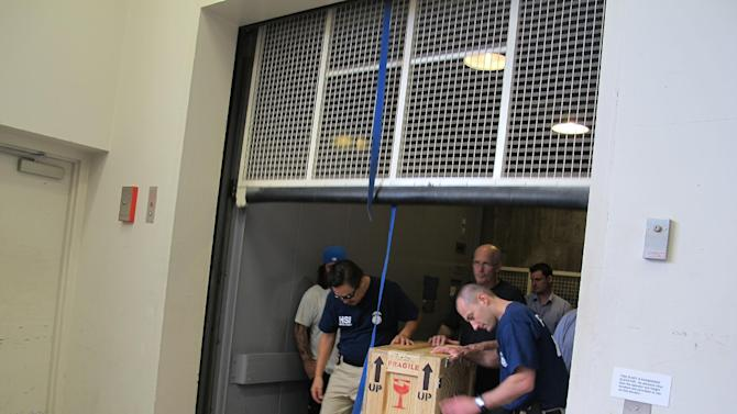 Homeland Security Investigations agents and workers from the Honolulu Museum of Art bring a crate up a freight elevator at the museum Wednesday, April 1, 2015, in Honolulu. The museum on Wednesday handed over seven rare artifacts that it acquired without museum officials realizing they were ill-gotten items, after an international investigation into antiquities looted from India and smuggled into the United States lead authorities to the museum. (AP Photo/Jennifer Sinco Kelleher)