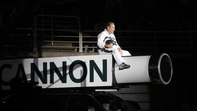 Michigan State coach Tom Izzo makes his entrance on top of a cannon before an NCAA college basketball scrimmage, Friday, Oct. 18, 2013, in East Lansing, Mich