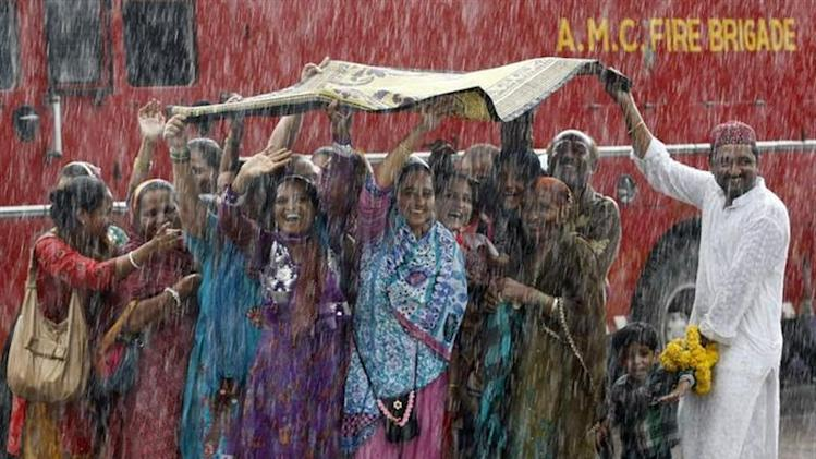 Relatives of Haj pilgrims wave in the rain, as they see off their relatives who are leaving Ahmedabad for Mecca in Saudi Arabia to take part in the annual religious Haj pilgrimage, September 26, 2013. REUTERS/Amit Dave
