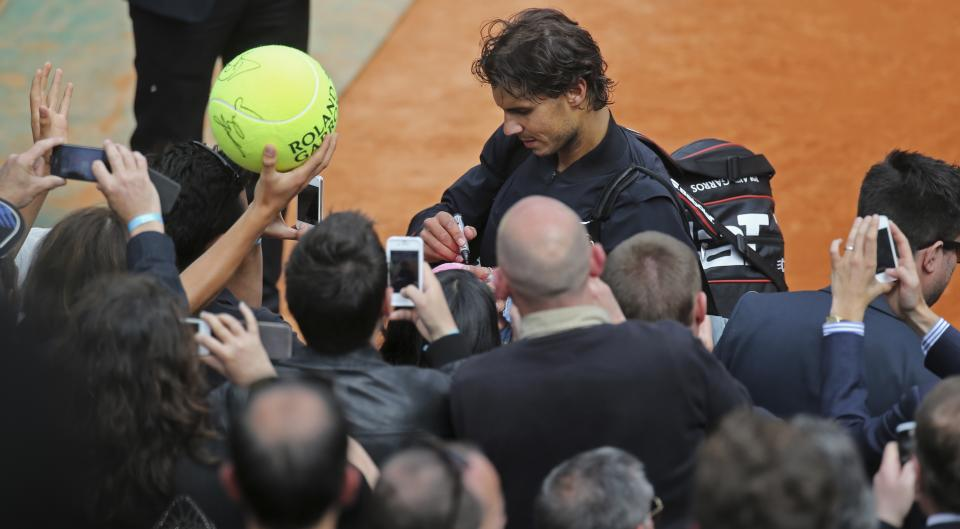 Spain's Rafael Nadal signs autographs after defeating Germany's Daniel Brands in their first round match of the French Open tennis tournament, at Roland Garros stadium in Paris, Monday, May 27, 2013. Nadal won in four sets 4-6, 7-6, 6-4, 6-3. (AP Photo/Michel Euler)