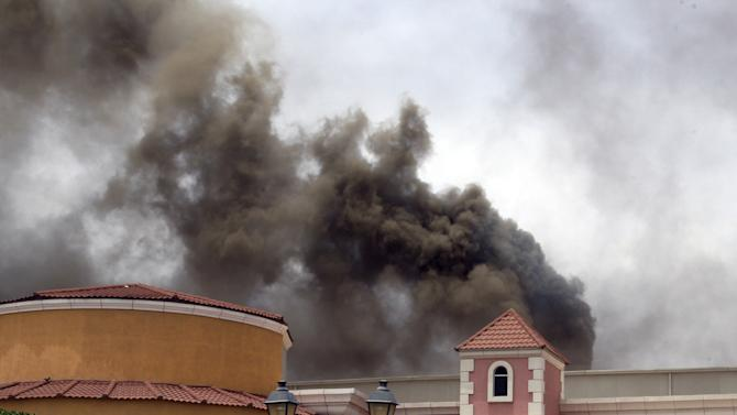 Smoke rises above the Villaggio Mall, in Doha's west end, as a fire took hold of the upscale mall in the Qatari capital of Doha Monday May 28, 2012. Qatar's Interior Ministry said 13 children were among 19 people killed in a fire that broke out at one of the Gulf state's fanciest shopping mall on Monday. The Villaggio opened in 2006 and is one of Qatar's most popular shopping and amusement destinations. It includes an ice skating rink and indoor Venice-style gondola rides. (AP Photo/Osama Faisal)