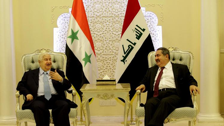Iraqi Foreign Minister Hoshyar Zebari, right, and his Syrian counterpart Walid al-Moallem talk during a meeting in Baghdad, Iraq, Sunday, May. 26, 2013. (AP Photo/Hadi Mizban, Pool)