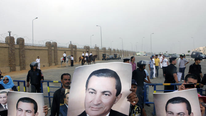 Egyptian pro -Mubarak supporters flash his posters outside police academy court in Cairo, Egypt, Monday, Sept.5, 2011. Mubarak, his two sons Alaa and Gamal, his security chief Habib el-Adly and six top police officers face third session of trial, on charges they ordered the use of lethal force against protesters during Egypt's 18-day uprising. Some 850 protesters were killed.  (AP Photo/Amr Nabil)