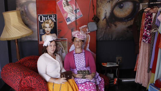 """In this photo taken Thursday, Jan. 10, 2013 visitors Yolandi Gloy, left, and Elize van der Nest, right, are photographed in period costume on the film set turned theme park, of the Afrikaans musical film """"Pretville"""" in Hartebeespoort, South Africa. The movie indulges in rock'n roll, vintage cars, greasers in sneakers, pin curl hairstyles and swing dresses, lots of pastel pink and blue, and double-thick strawberry milkshakes with extra cream. (AP Photo/Denis Farrell)"""
