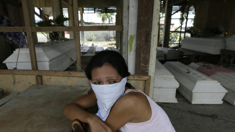 Arlene Barcelona sits at a damaged public market for the wake of her mother Felicitas who was killed at the height of Tuesday's typhoon Bopha at New Bataan township, Compostela Valley in southern Philippines Saturday Dec. 8, 2012. Search and rescue operations following a typhoon that killed nearly 600 people in the southern Philippines have been hampered in part because many residents of this ravaged farming community are too stunned to assist recovery efforts, an official said Saturday. (AP Photo/Bullit Marquez)