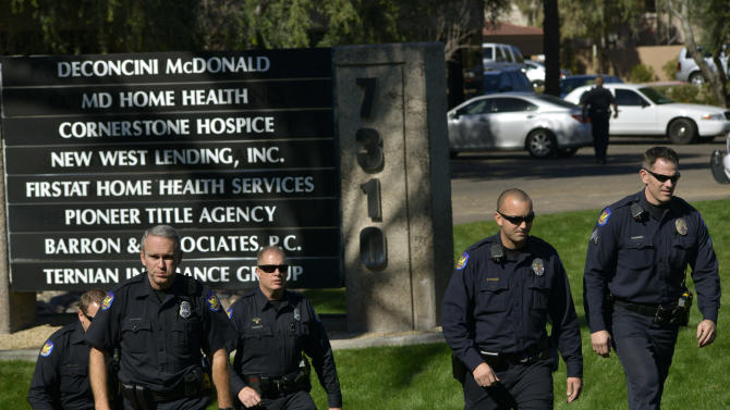 Police officers leave an office building after a shooting at the building in Phoenix on Wednesday, Jan. 30, 2013. A gunman opened fire at the Phoenix office building, wounding three people, one of them critically, authorities said. Police were searching for the shooter. (AP Photo/Patrick Sison)