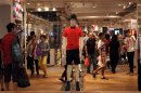 Shoppers walk inside flagship store of Japanese fashion house Uniqlo at Hong Kong's Causeway Bay shopping district